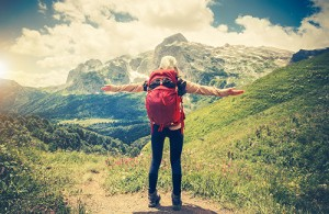 Traveler Woman with backpack hands raised mountaineering